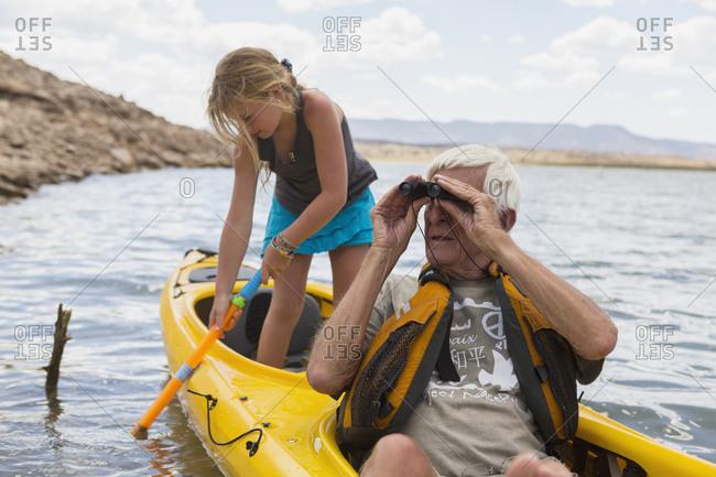 Elderly man kayaking on a lake with his granddaughter