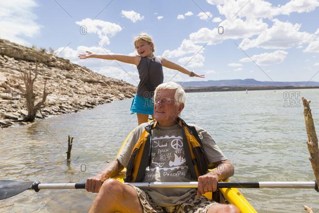 Senior man kayaking on a lake with his granddaughter