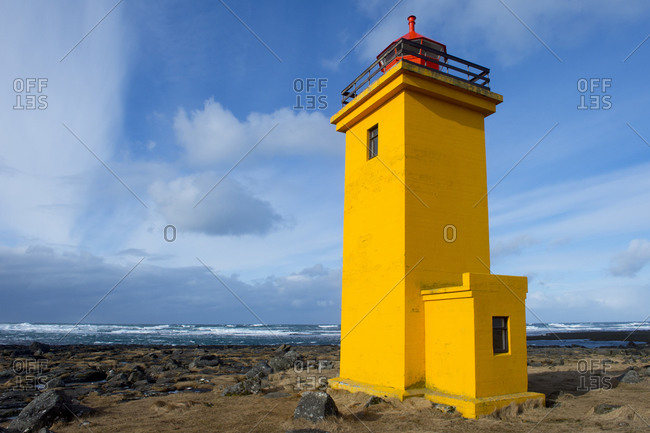 View of a lighthouse on a seashore in rural Iceland