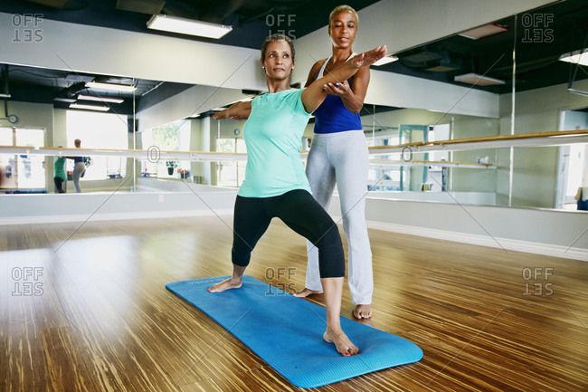 Women practicing with a yoga teacher in a studio