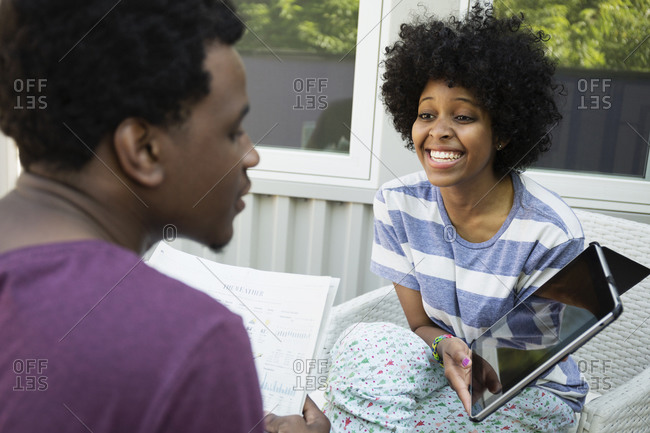 Couple using tablet computer together on porch