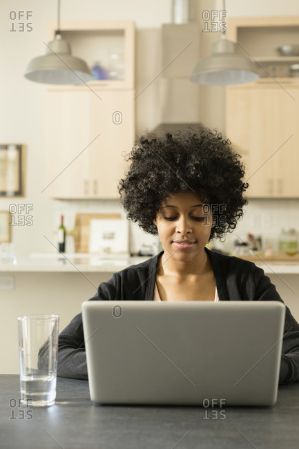 Young woman using laptop at breakfast table