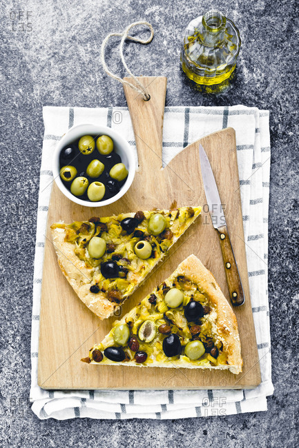 Slices of raisin and olive foccacia on a cutting board