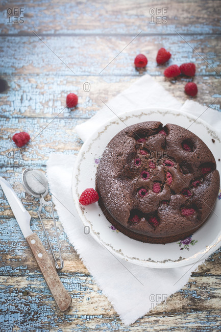 Round chocolate cake with red raspberries
