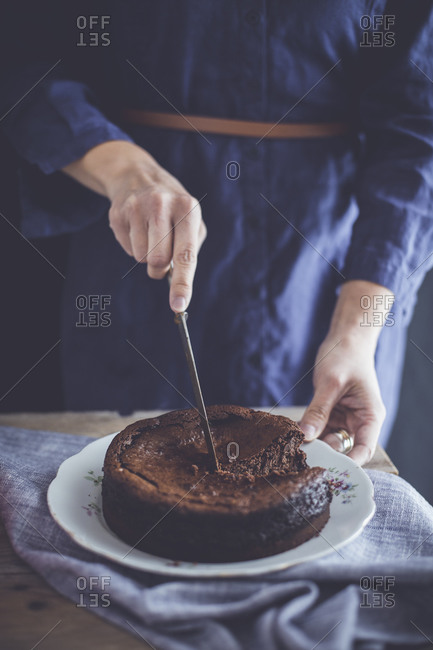 Woman slicing into a chocolate cheesecake