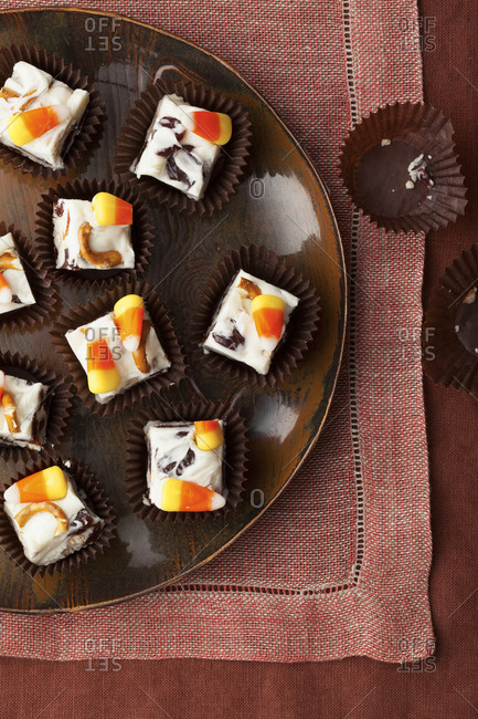 Overhead of candy corn white chocolate fudge squares in paper cups on platter