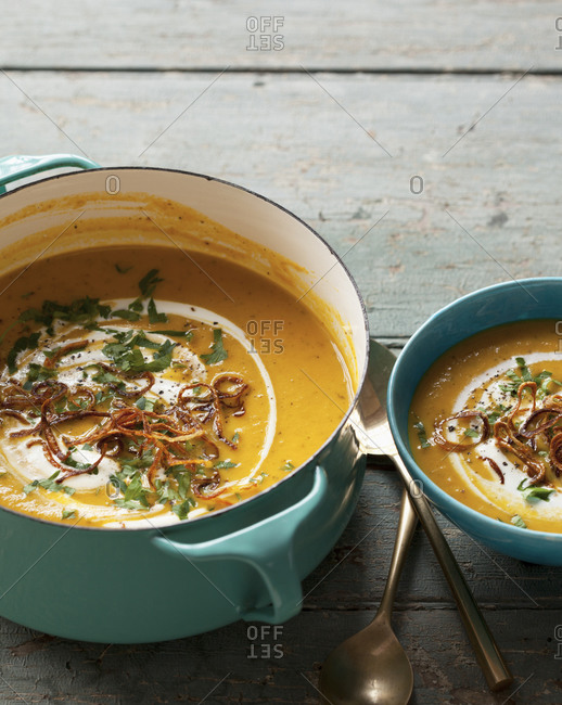 Pot of carrot and butterbean soup next to a bowl of soup on a wooden surface