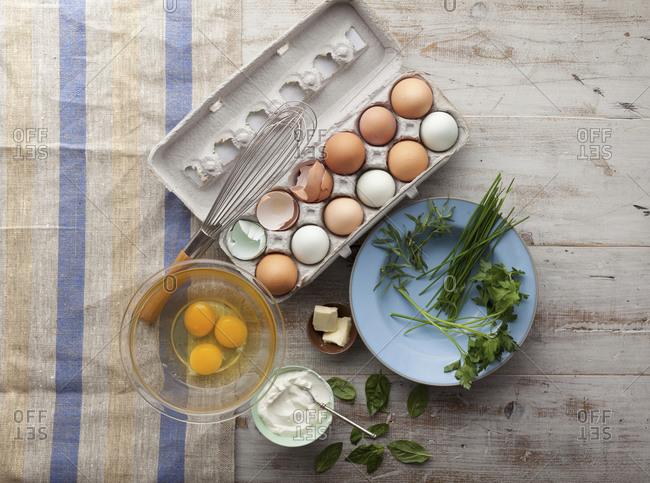 Overhead view of ingredients for herbed scrambeled eggs with egg carton
