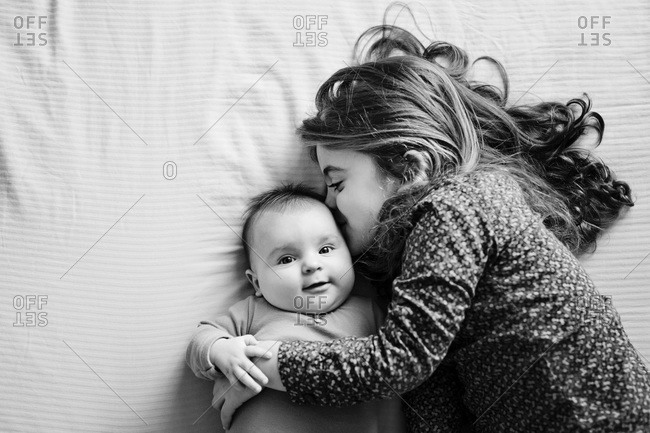 Girl hugging a baby while lying on a bed