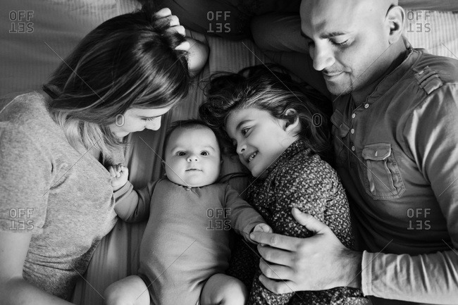 Mother, father and sister gaze lovingly at baby girl