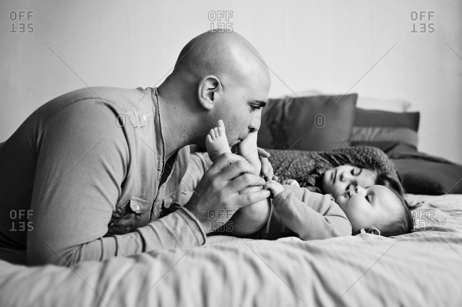 Father playing with children on bed