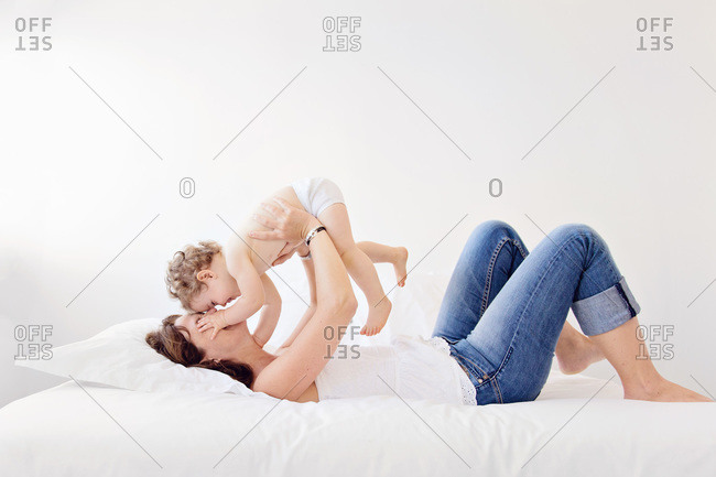 Mother and child playing on bed