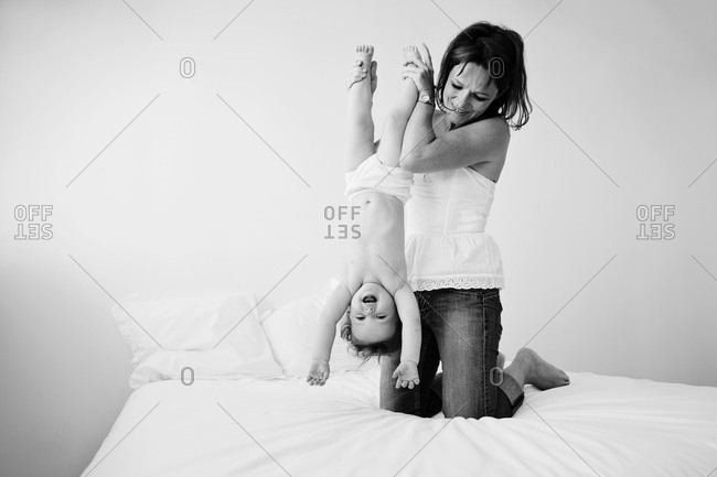 Mother holding her laughing baby upside down on bed