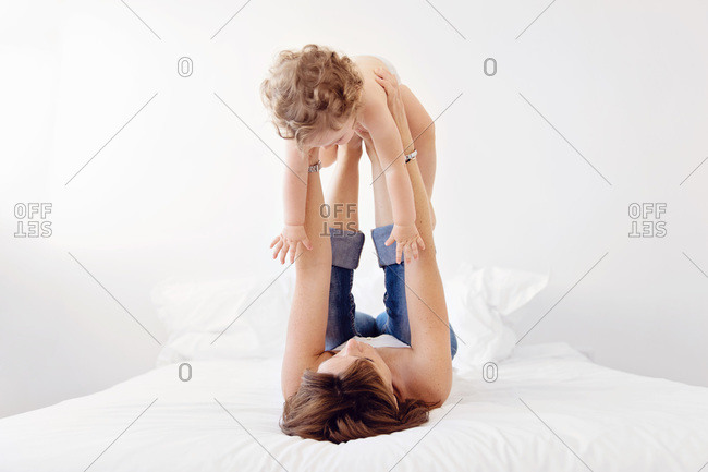 Woman lying on bed, lifting baby up in the air