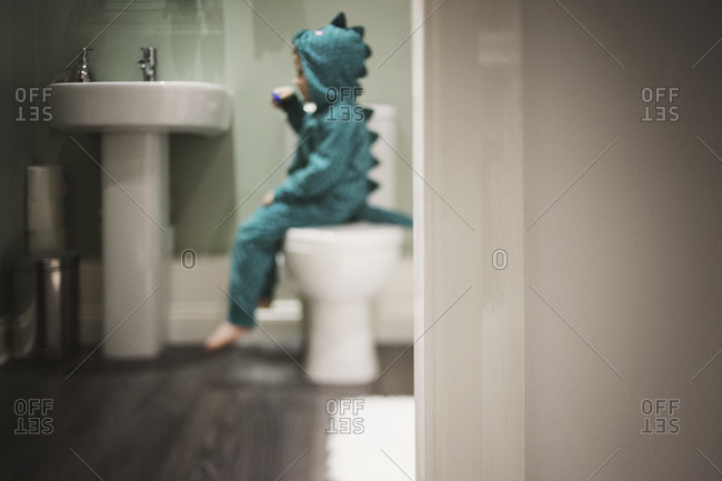 Child in dinosaur costume brushing his teeth while sitting on the toilet