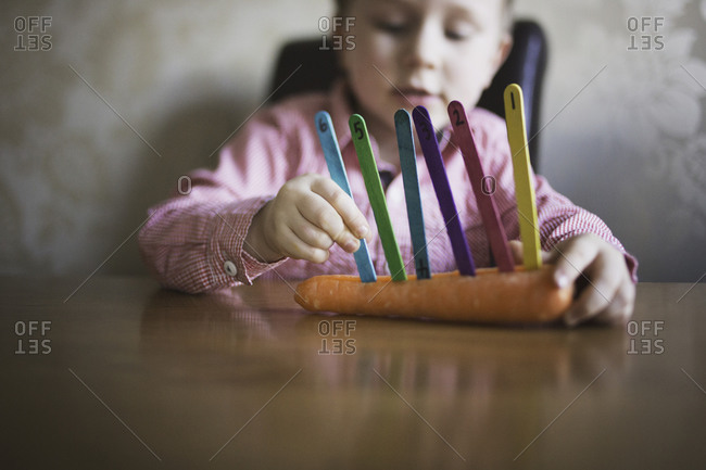 Child lining up colored craft sticks in a cut carrot