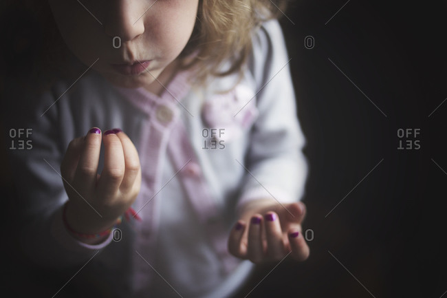 Young girl blowing on her wet purple fingernail polish