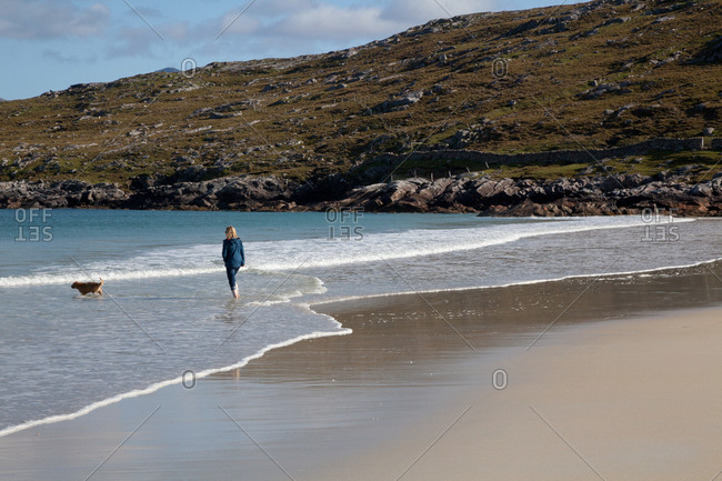 Woman and dog alone on beach, Isle of Harris, Hebrides, Scotland