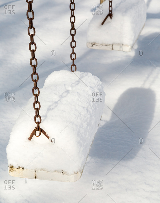 Close-up of playground swings covered with snow