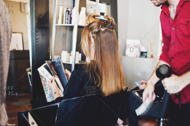 Woman reading a magazine in a salon chair while stylist dries her hair