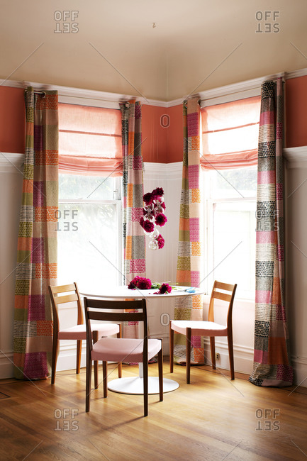 Dining table between two windows in a pink and orange room