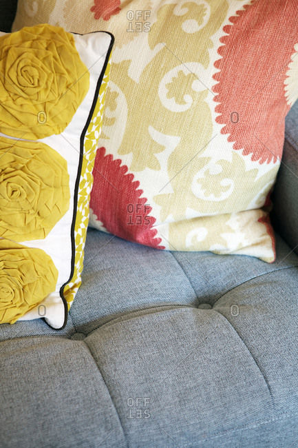 Close-up of throw pillows on a blue upholstered sofa