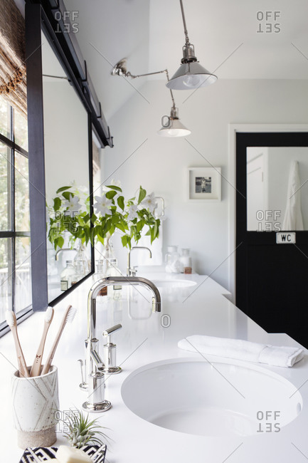 Modern bathroom with white countertop in front of windows