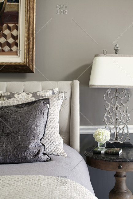 Close-up detail of gray bed with upholstered headboard and stone-topped side table