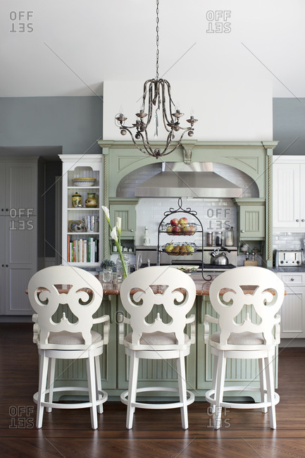Kitchen with gray, green and white color scheme and ornate backed counter seating