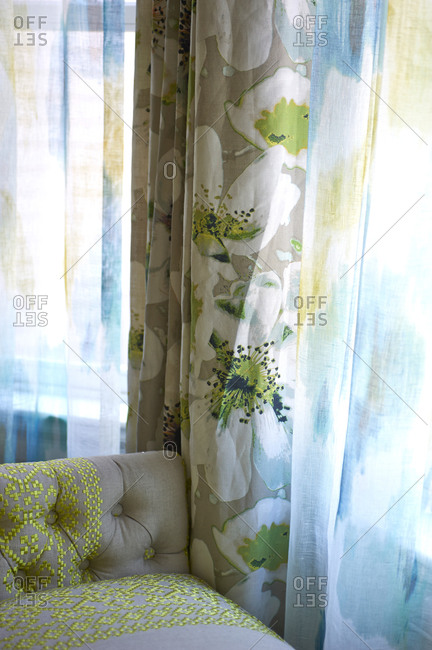 Tan, white and green floral drapes next to tan and green sofa