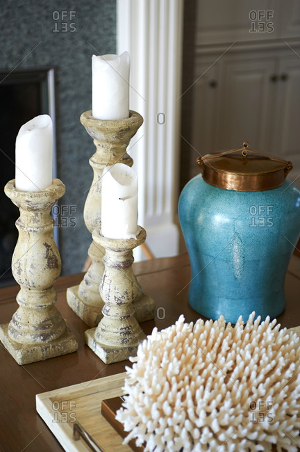 Tabletop arrangement of candles, coral, and blue jar