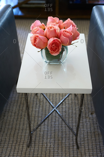 Table with roses between two leather chairs