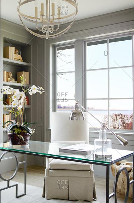Elegant glass desk in front of a window