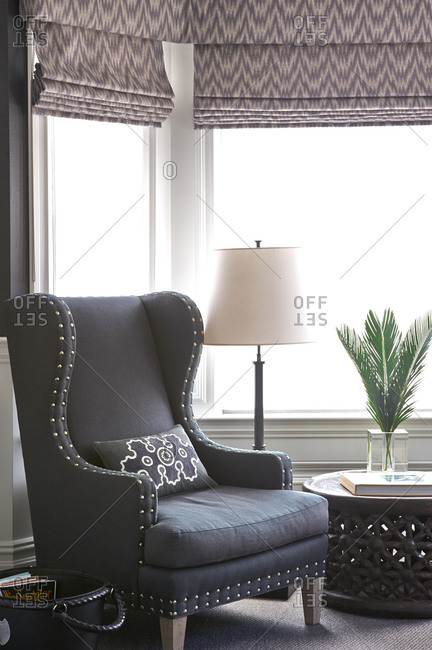 Gray wingback chair in front of bay windows