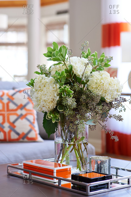 White flower arrangement in living room with orange and gray color scheme