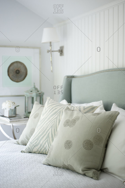 An assortment of gray pillows on bed with soft blue upholstered headboard