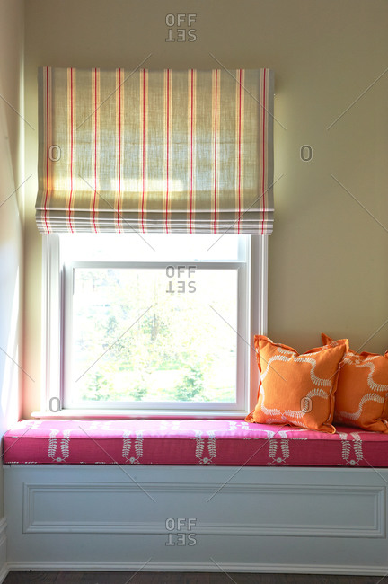 A pink cushioned window seat with orange pillows
