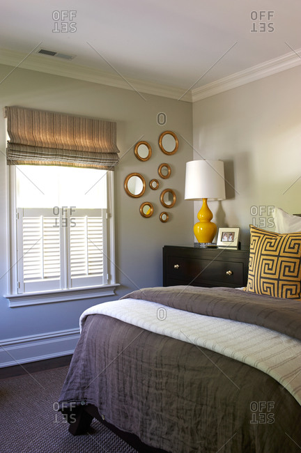 A gray bedroom with yellow accents and gold circle mirrors on the wall