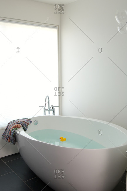 Modern free-standing white egg-shaped bathtub with rubber duck