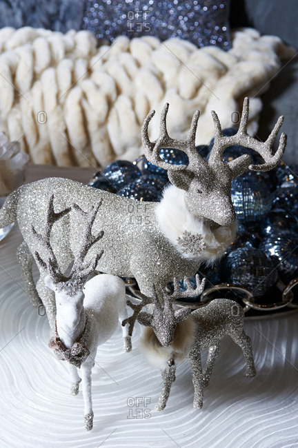 Tabletop display of glittered reindeer and a bowl of blue Christmas ornaments