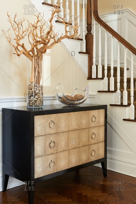 Chest of drawers and vase with branch at bottom of stairs