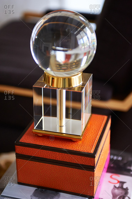 A modern crystal sphere on top of an orange box on coffee table