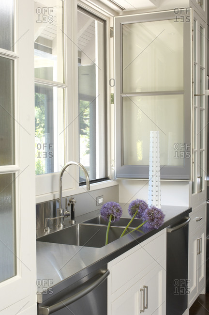 Clean, modern gray and white kitchen with allium flowers in the sink