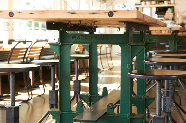 Industrial-style workbench and stool seating in a casual restaurant