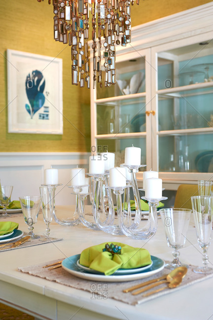 Green and blue table settings in a gold and white dining room