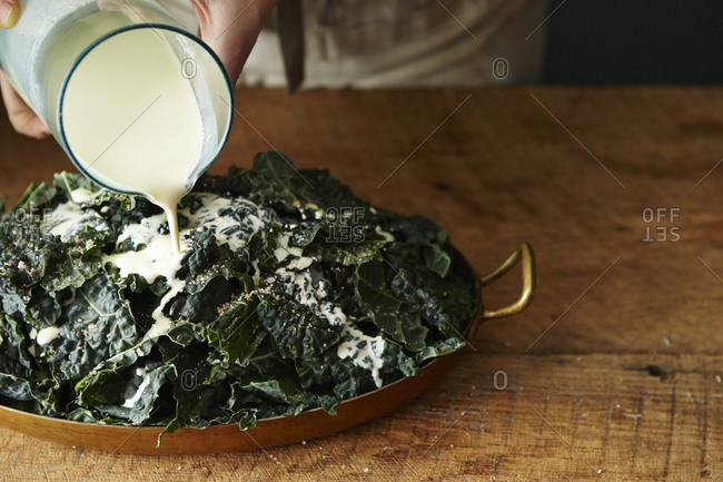 Pouring heavy cream over kale dish