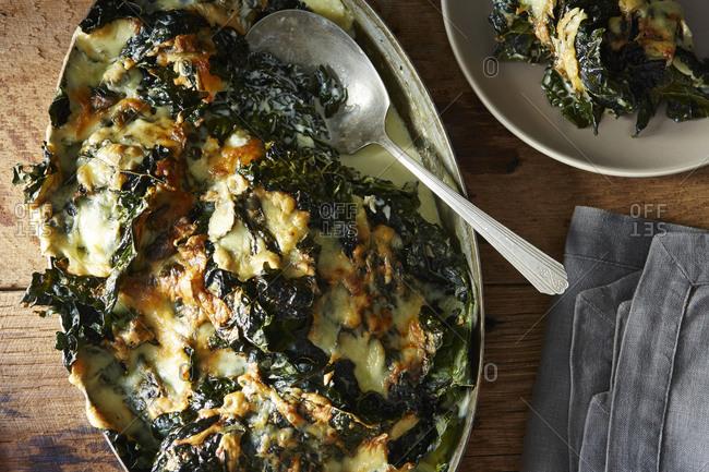 Serving baked kale gratin dish