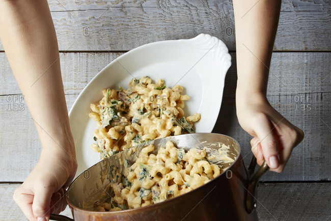 Pouring homemade macaroni into serving dish