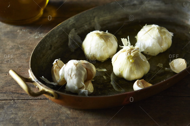 Whole garlic bulbs in oil in casserole