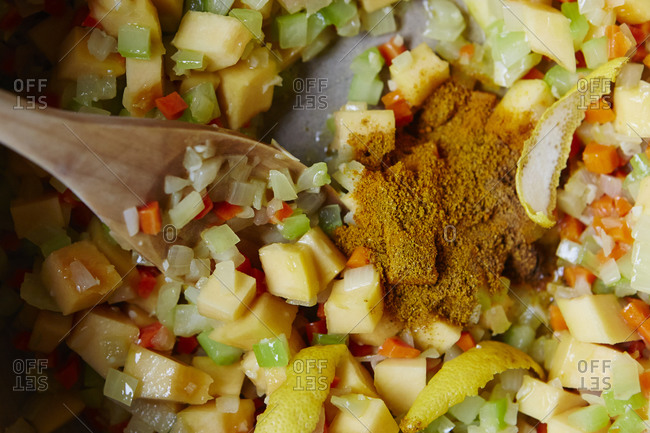 Seasoning added to squash and veggies cooking in pot